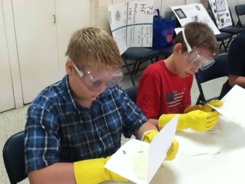 Middle school students performing a science experiment while wearing lab goggles