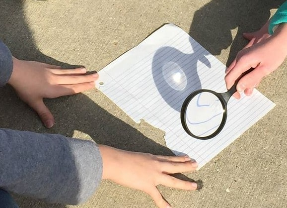 With adult supervision, students attempt to focus the sun's rays to burn a hole in a piece of paper